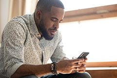 Black male looking at mobile phone